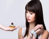 אישה מנסה לעמוד בפיתוי של אכילת עוגה